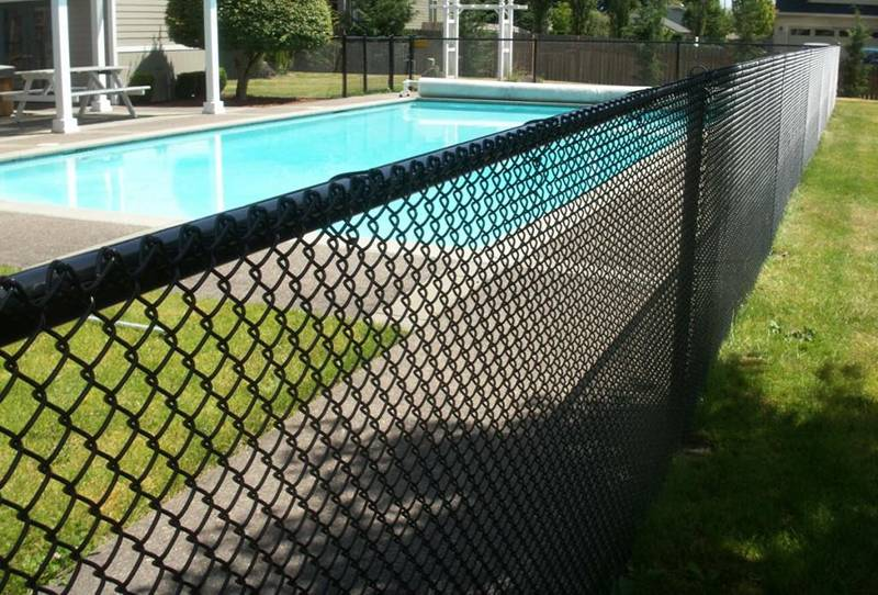 Black vinyl-coated chain link swimming pool fence.