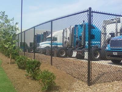 A black commercial chain link fence in front of many trucks.