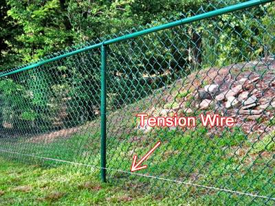 Galvanized tension wire installed in the bottom of green vinyl-coated chain-link fence.