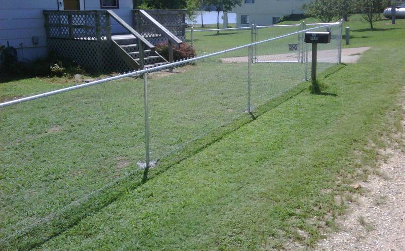 Standard galvanized chain link fence with swing gate.