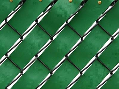 Green fence weave inserted within black chain link fence.