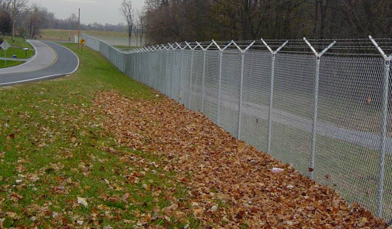 Commercial chain link fence along a busy highway.