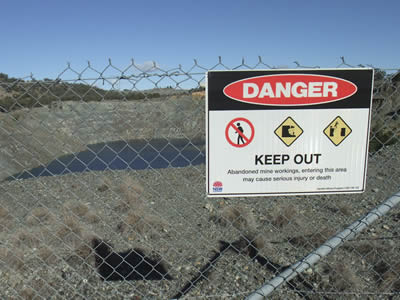 An abandoned mine area became a pool as the time pass by, chain link fence with warning board beside the abandoned area to warn people should not enter.