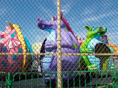 Colorful animal module swivel houses encircled by gold chain link fence, the chain link fence is taller than animal module houses and also with shorter green metal fence reinforcement.