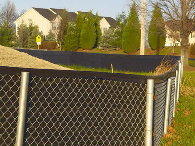 Chain link silt fence consists of black filter fabric sheet and chain link fence, around the hay stacked area in the residential area.