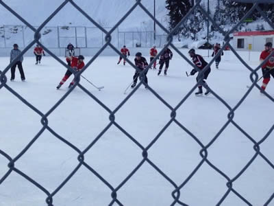 Chain link fence around ice hockey field, and two teams are fighting fierce.