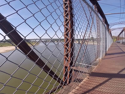 A metal bridge with chain link railing across a deep and wide river.
