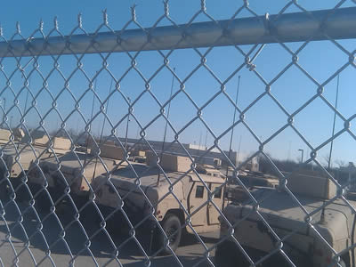 Chain link fence around military camp, and a row of orderly tanks behind the fence.
