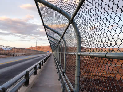 Expressway is located at barren rocky area, with chain link fence on two sides.