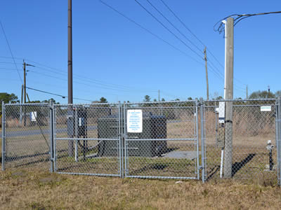 Framed chain link portable security fencing around substation near a road.