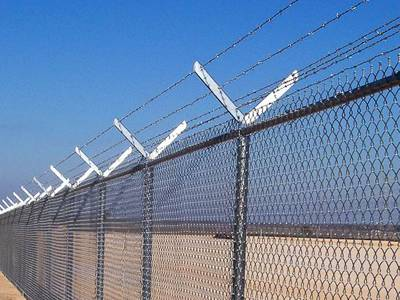 Six strands of barbed wire over chain link fence.