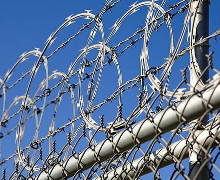 Barbed wires and razor wires are installed at the top of chain link fence for security.