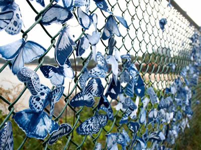 Hundreds of blue butterflies made from  cotton hanging on chain link fence.