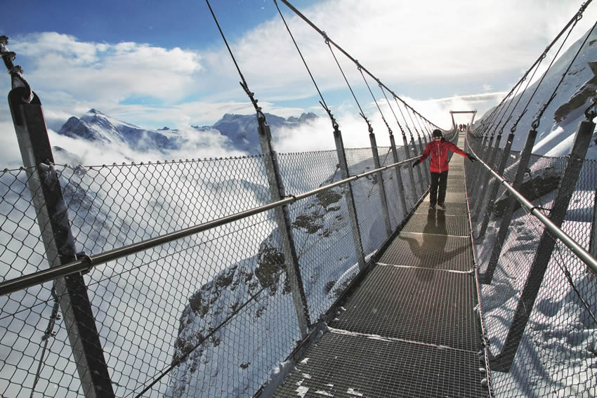 Suspended walkway with chain link fence in the snow peak of the mountain, a man in red cloth walk on it.