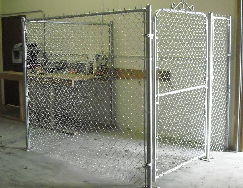 A chain link fence enclosure with single walk gate.
