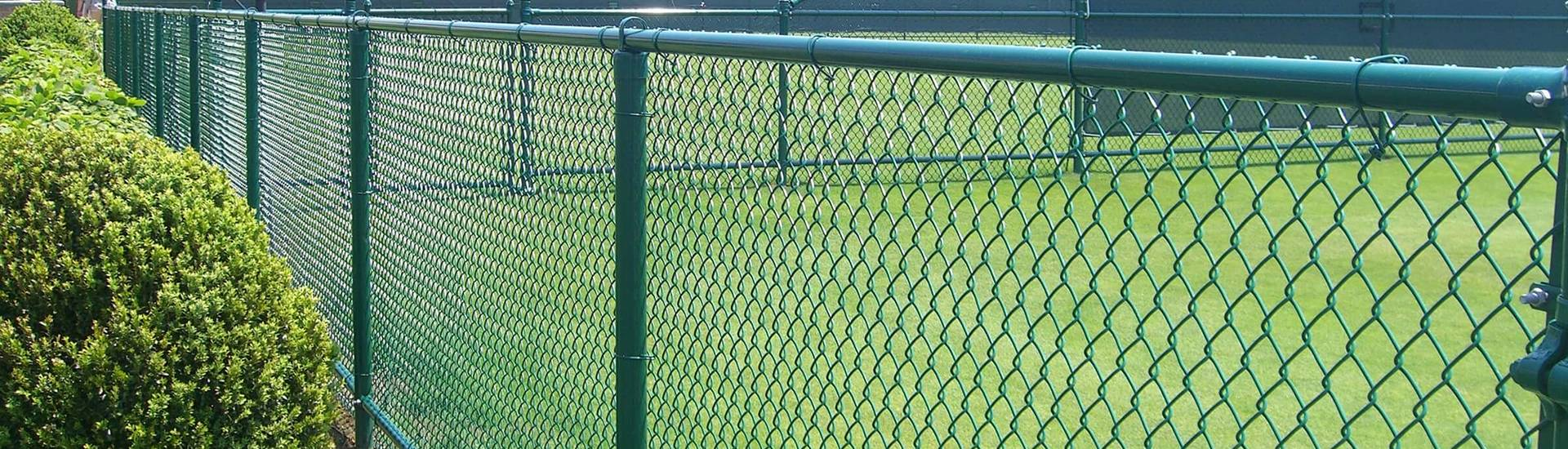 Green color chain link fences are installed on the grassland.