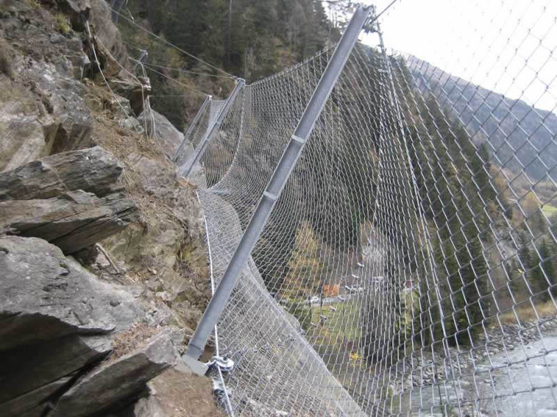 Chain link rockfall protection barrier upper a river.