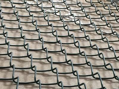 Unfolded green chain link helideck mesh fence.