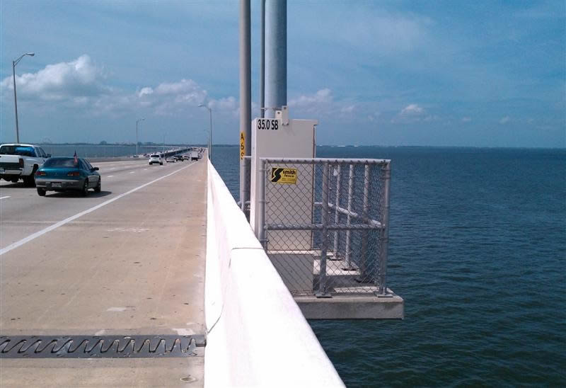 A electric power box beside cross-sea bridge and stretches out to the sea was surrounded by chain link fence.