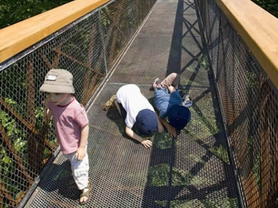 Suspended walkway with chain link fence railing and perforated metal floor heavy metal reinforcement.