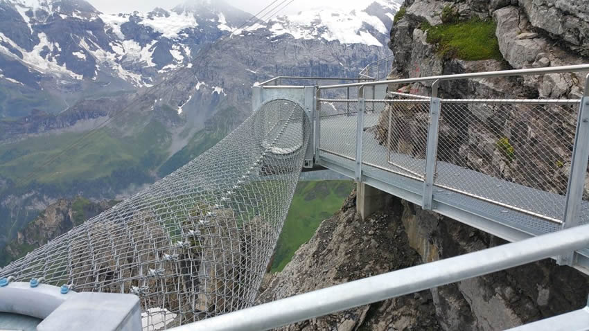 Cylindrical chain link thrill walk is on the halfway of the cliff.