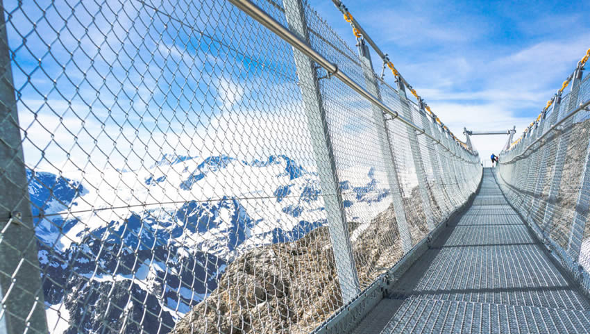 Metal walkway with chain link fence railing at the peak of mountain.