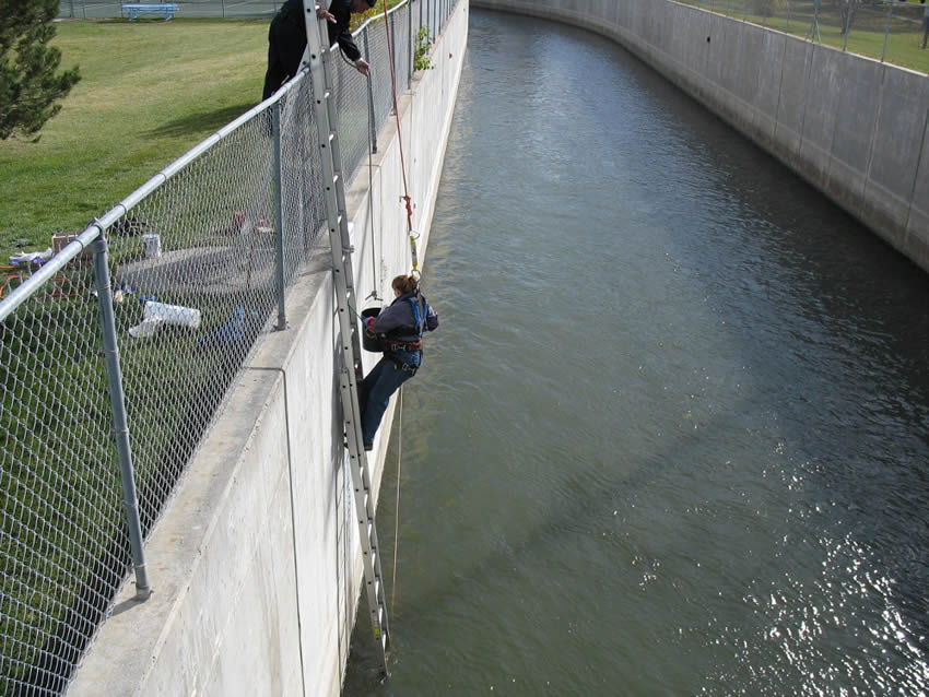 Drainage river enclosure consists of concrete wall and chain link fence. A person goes down to the drainage river by using folding ladder to pick up some water.