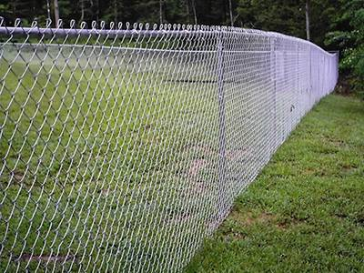Galvanized chain link fence with knuckle selvage used in park.