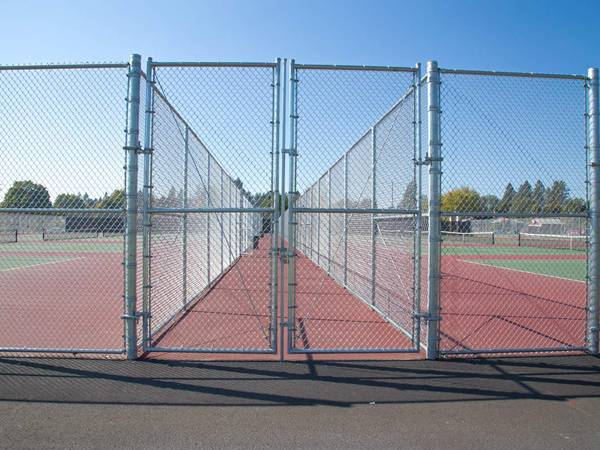Two sports fields surrounded and separated by galvanized chain link fence.