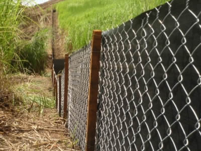 Silt fence consists of chain link fence and black plastic sheeting in the suburbs.