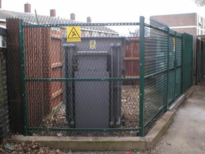 Green electric security chain link fence around a personal substation.