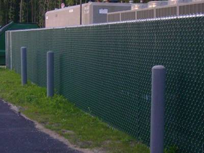 Green chain link fence privacy slats for residential fence along a busy road.
