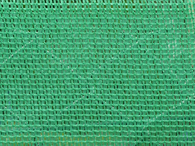 Small mesh holes green woven fabric net and the chain link fence behind.