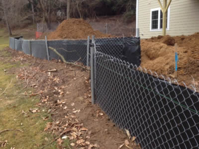 Silt fence consists of chain link fence and black fabric sheet around the building.