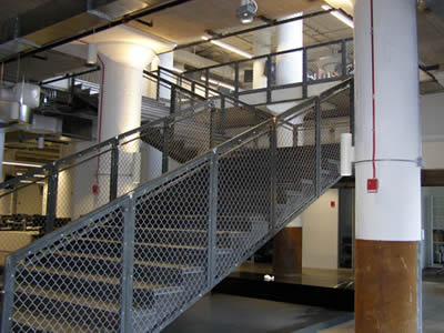 Indoor stair handrail with framed chain link fence for security protection.