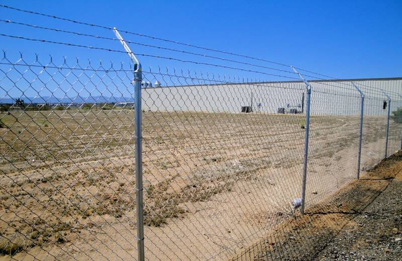 Galvanized chain link fence with three strands of barbed wire for security.