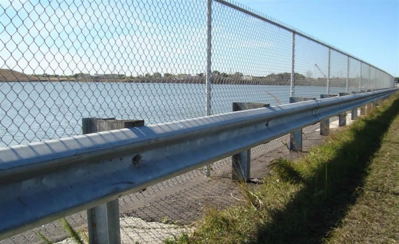 Chain link fence installed at the coastline, and a dwarf metal railing to reinforce the chain link fence.