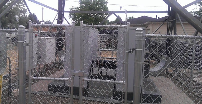 Framed galvanized security chain link fence and gates around power generators, and the chain link gates slightly higher than the periphery fence.
