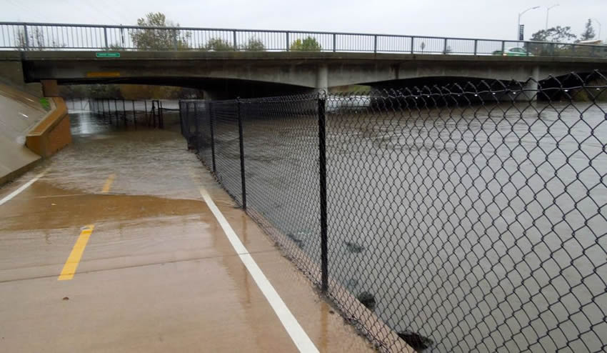 A road with chain link security fence under a bridge, and now the road was blocked by flood.