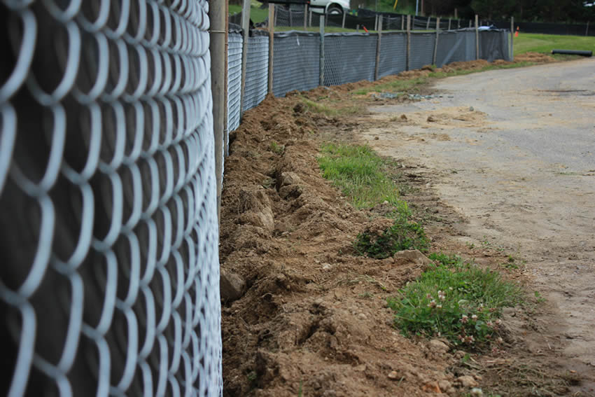 Chain link silt fence consists of black fabric sheet and chain link fence beside the road.