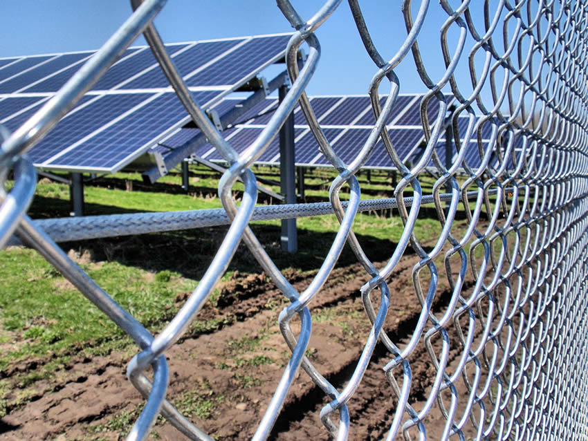 Galvanized chain link security fence around solar panel farm.