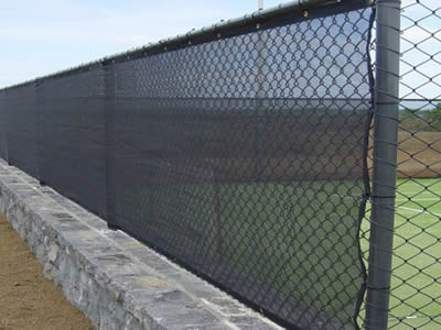 Windbreak fencing in a bare land was made of chain link fence and black woven fabric net.