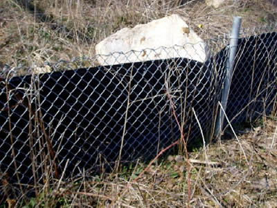 Chain link silt fence consists of chain link fence and black geotextile in the wasteland.