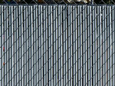 White single wall bottom locking slats for black chain link fence.